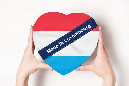 Inscription Made in Luxembourg, the flag of Luxembourg. Female hands holding a heart shaped box. White background. Stockfoto
