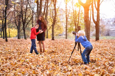 Little blond boy with a big SLR camera on a tripod. Photographs a pregnant mother and son. Family photo session
