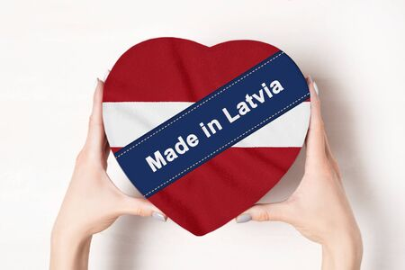 Inscription Made in Latvia, the flag of Latvia. Female hands holding a heart shaped box. White background.