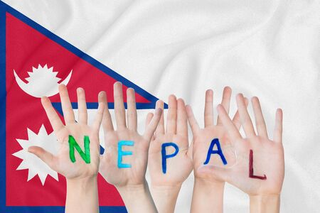 Inscription Nepal on the childrens hands against the background of a waving flag of the Nepal