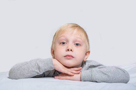 Blond boy lies with his head in his hands. White background