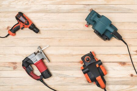 Set of hand carpentry power tools for woodworking lies on a light wooden background. Directly above.