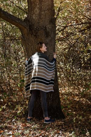 Young woman hugging a tree. Unity with nature, autumn forest