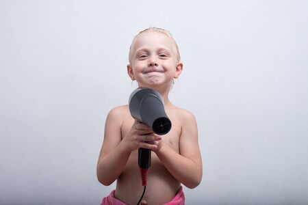 Smiling blond boy with wet hair and a hairdryer in hands. White background