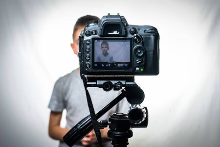 Schoolboy is filming himself on a camcorder. Young video blogger. White background. Foreground camera