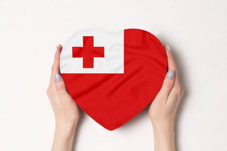 Flag of Tonga on a heart shaped box in a female hands. White background
