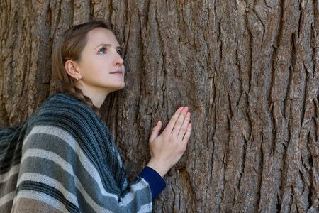 Young woman leaned against the trunk of a large tree. Unity with nature