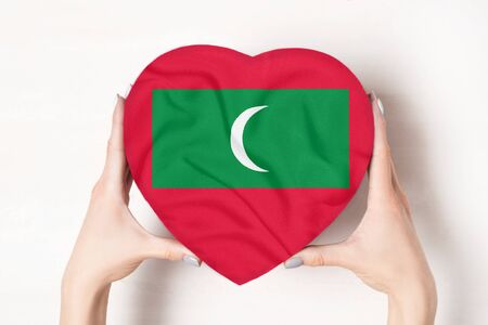 Flag of Maldives on a heart shaped box in a female hands. White background Imagens