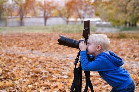 Little blond boy shoots with a large SLR camera on a tripod. Photo session in the autumn park