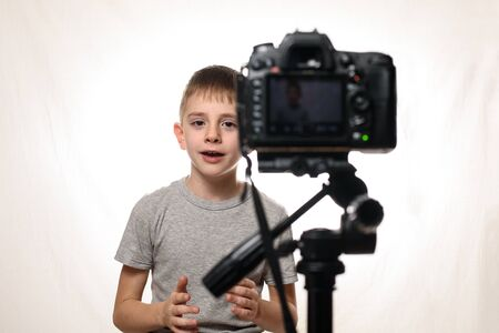 Schoolboy is saying something on a camcorder. Young video blogger. White background
