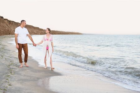 Young married couple walks along the sea coast. Pregnancy. Pre-sunset time Stock Photo