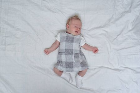 Sleeping newborn girl in a dress on a white sheet. Top view. Space for text