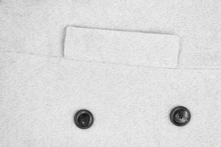 White textured woolen coat fabric with a lapel pocket and two buttons. Close-up