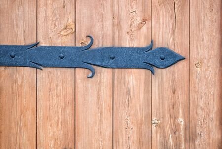 Antique metal forged door sheds on a raw wooden door. Close up.