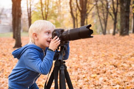 Little blond boy takes pictures on a SLR camera. Autumn Park