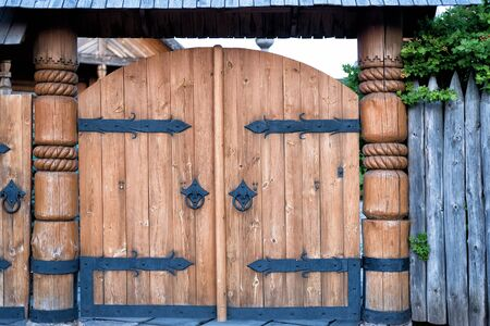 Vintage wooden gate with wrought iron elements.