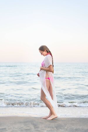 Young pregnant woman is standing on the seashore and hugging her belly. Enjoying the moment.
