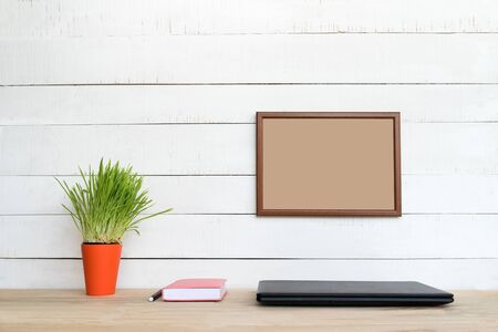 Empty frame on white wall. Closed laptop, notebook and pen. Green houseplant. Home workplace. Place for text