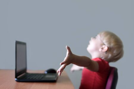 Blurred portrait of a blond boy at a laptop. Joy, end of work