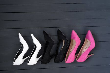 Three pairs of different high heel shoes. Black wooden background. Banco de Imagens