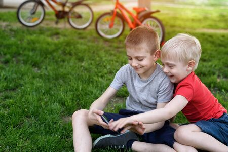 Two boys are gaming on the smartphone while sitting on the grass. Bicycles in the background Stockfoto