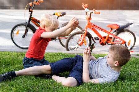 Two boys are photographed on a smartphone while sitting on the grass. Rest after cycling, bicycles in the background