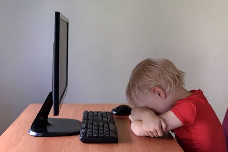 Tired little blond boy sleeping on a table under the monitor PC. Internet and preschooler