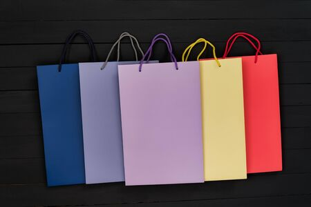 Five paper multi-colored shopping bags on black wooden background. Top view.