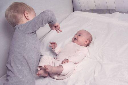 Blonder älterer Bruder spielt mit seiner kleinen Schwester. Kinderinteraktion Standard-Bild