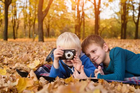 Two little brothers take a pictures on the camera. Lying in yellow autumn leaves. Fall day