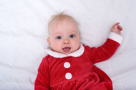 Portrait of cute little baby in a santa costume. Lying on white background. Christmas concept