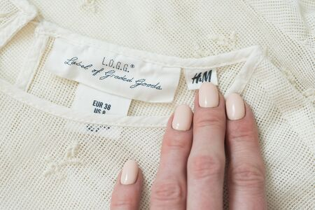 KHARKIV, UKRAINE - September 19, 2019: White HM tag and a female hand on embroidered clothing. Close-up