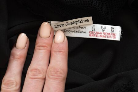 KHARKIV, UKRAINE - September 19, 2019: Tag Love Josephine with female hand on black clothes. Close-up 報道画像
