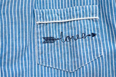 KHARKIV, UKRAINE - September 19, 2019: Embroidered inscription love on blue striped pocket of clothing. Close-up