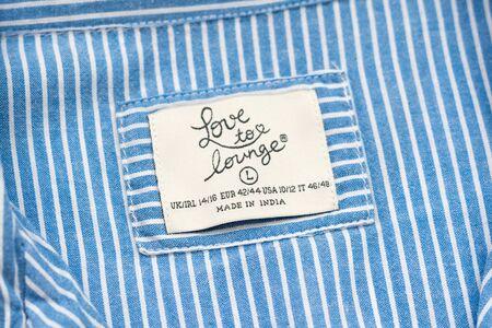 KHARKIV, UKRAINE - September 19, 2019: White Love to lounge tag on blue striped clothing. Close-up 報道画像