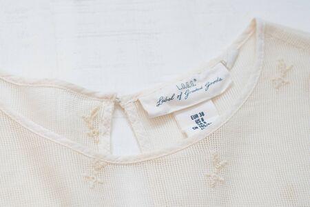 KHARKIV, UKRAINE - September 19, 2019: White tag L.O.G.G. on embroidered clothes. Close-up