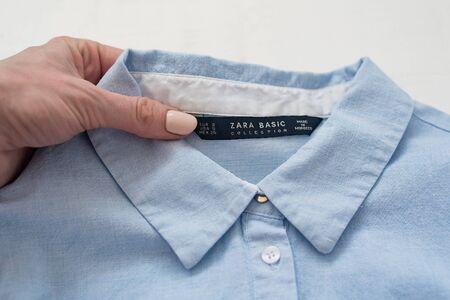 KHARKIV, UKRAINE - September 19, 2019: Black tag ZARA BASIC in a female hand, collar of a blue shirt. Close-up