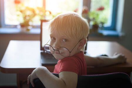 Portrait of a smiling blond boy with glasses at a laptop. Break