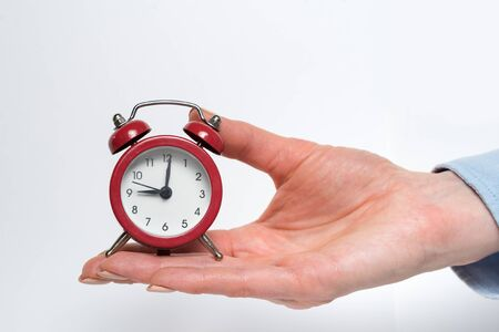 Red alarm clock in a female hand on a white background. 写真素材