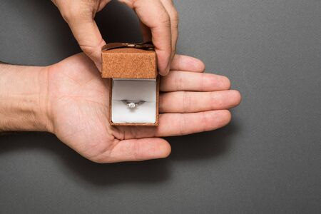 Open brown jewelry box with ring in a male palm. Present. Black background