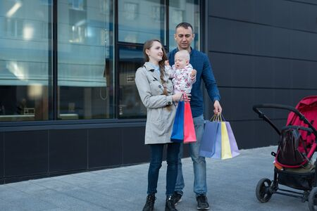 Young mother with little daughter on the arms. Father with shopping bags in hand. Family shopping. Mall on background 写真素材