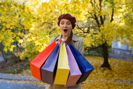 Happy young woman shopaholic with colorful bags near mall. Walking on the street.