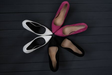 Womens heels of different colors are arranged in a circle. Black wood background. Fashion concept