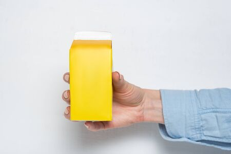 Yellow carton box or packaging of tetra pack in a female hand. White background