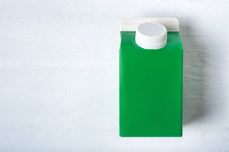 Green carton box or packaging of tetra pack with a cap. White background