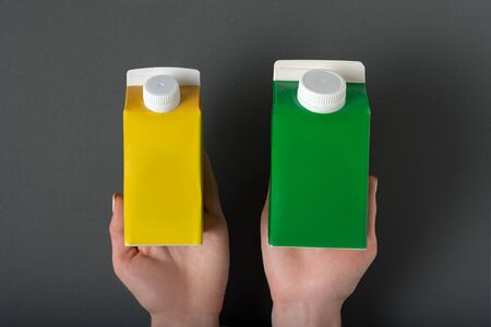 Yellow and green carton box or packaging of tetra pack in a female hands. Black background Stock fotó