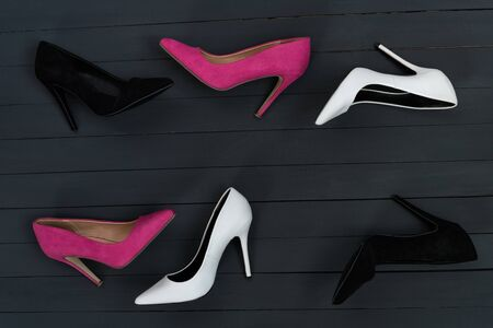 Womens high heel shoes in different colors. Black wood background. Fashion concept Reklamní fotografie