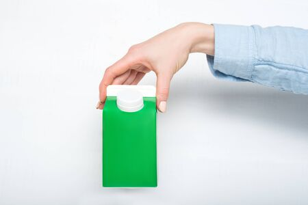 Green carton box or packaging of tetra pack with a cap in a female hand. White background