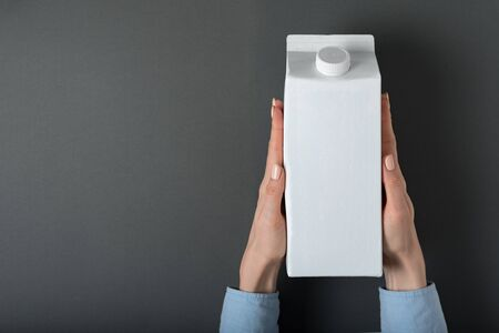 White carton box or packaging of tetra pack with a cap in a female hands. Black background