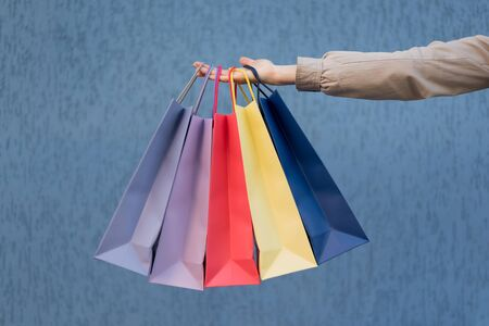 Five colored bags for shopping in a female hand. Close-up. Shopping Stock Photo